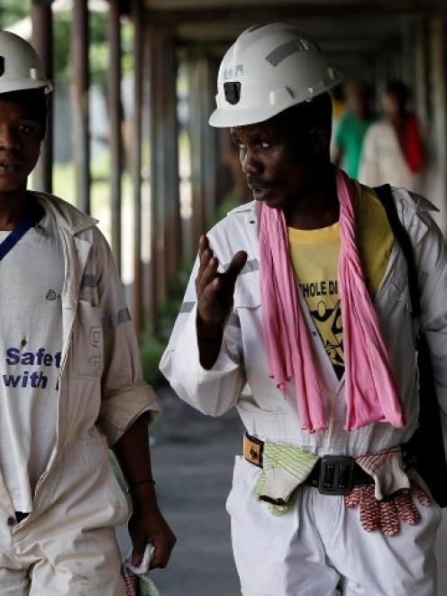 Miners walk at the end of their shift at the Anglo Platinum's Khuseleka shaft 1 mine in...