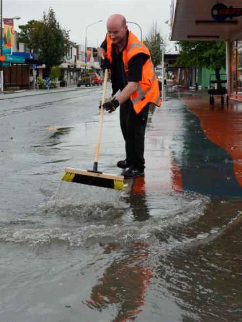 Mitre 10 assistant manager Ricky Bray, of Mosgiel, works to clear floodwater threatening Gordon...