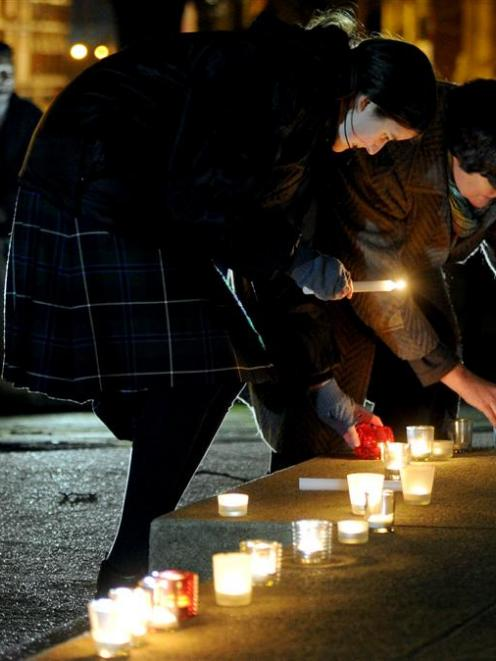 Moira Thomson (left) and the Rev Anne Thomson, of First Church, place candles at a peace vigil at...