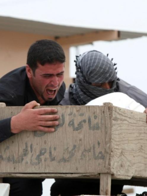 Mourners cry as they hold the coffin of a relative who was killed in the attack. REUTERS/Alaa Al...