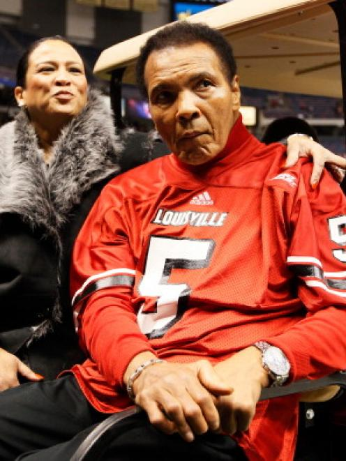 Muhammad Ali and his wife Lonnie Ali ride a golf cart on to the field to represent the Louisville...