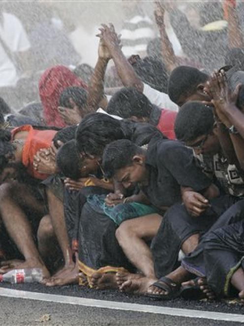 In this 2007 file photo, ethnic Indians sit along a roadside as they are sprayed water by riot...