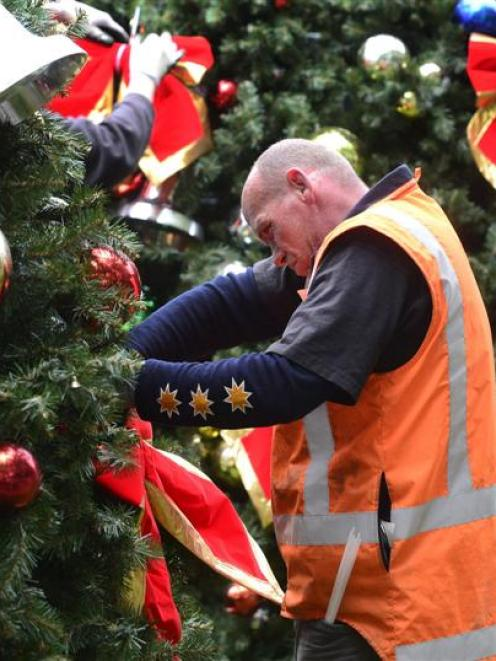 Nate Cummings of Dunedin applying the decorations to the Octagon Christmas Tree before going up...