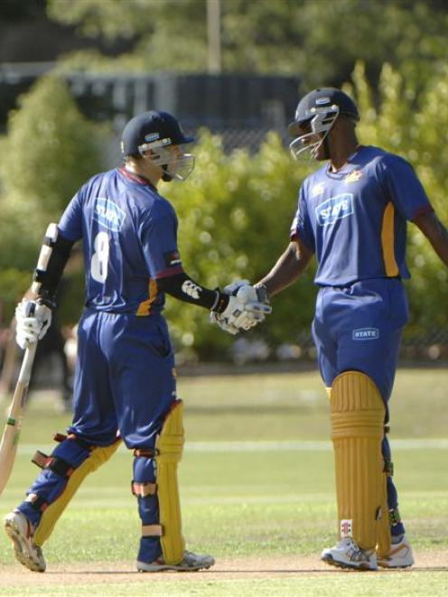 Nathan McCullum (left) is congratulated by Dimitri Mascarenhas after reaching his 50 at the...