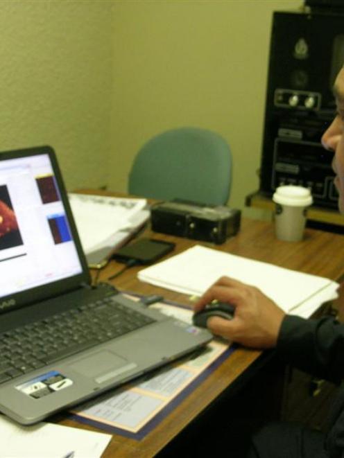 Navy Warrant Officer hydrographic survey technician Bernie Reihana looks at an item of interest...