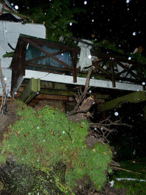 Neighbour Thomas Knight looks at where a tree smashed through a Kaitaia house, trapping a woman...