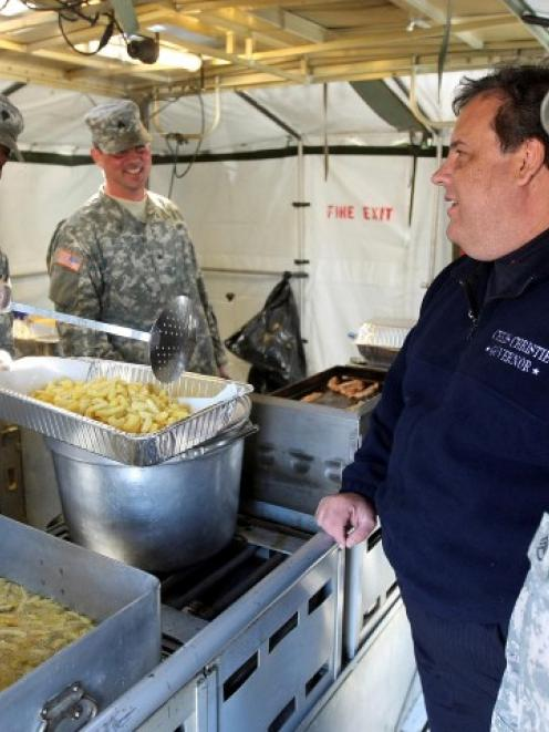 New Jersey Governor (C) Chris Christie talks with New Jersey National Guard cooks while they...
