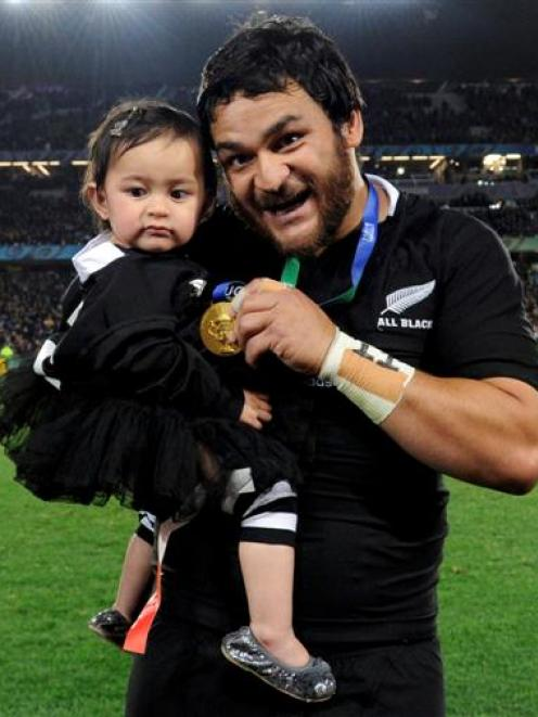 New Zealand All Blacks' Piri Weepu poses with his daughter Keira and his gold medal.   REUTERS...