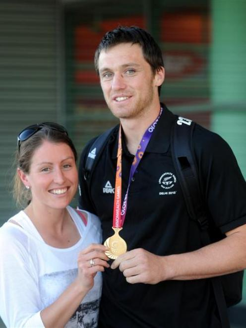 New Zealand rugby sevens player Ben Smith shows his Commonwealth Games gold medal to partner...