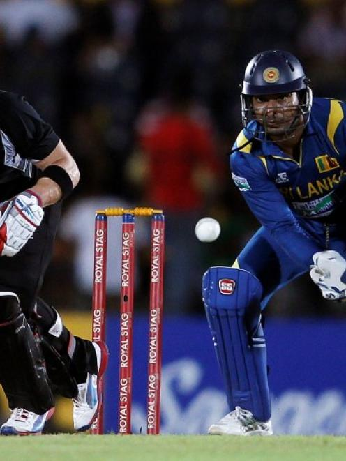 New Zealand's Brendon McCullum (L) plays a shot as Sri Lankan wicketkeeper Kumar Sangakkara...