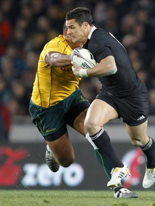 New Zealand's Dan Carter looks to fend off the tackle of Australia's Sekope Kepu during the Tri...