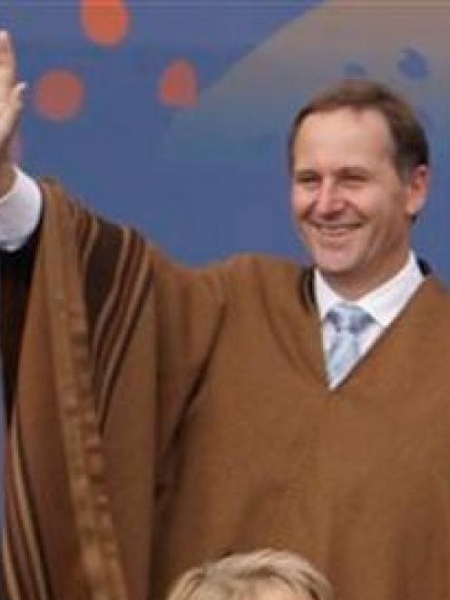 New Zealand's Prime Minister John Key wears a traditional Peruvian poncho as he waves during the...