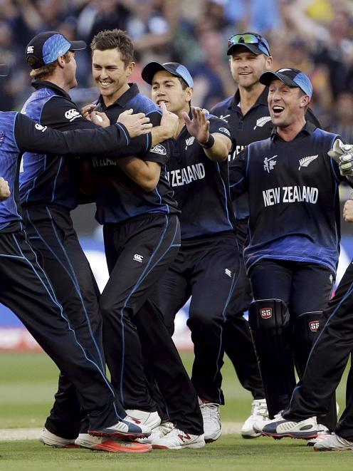 New Zealand's Trent Boult (C) is surrounded by team mates as they celebrate dismissing Australia...