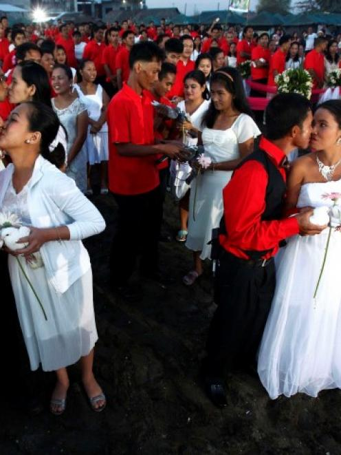 Newlywed couples kiss during a mass wedding ceremony at Rosario town, Cavite city, south of...