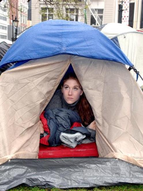"""Niamh O'Flynn, part of the """"Occupy Dunedin"""" protest, looks out at the rain from her tent..."""