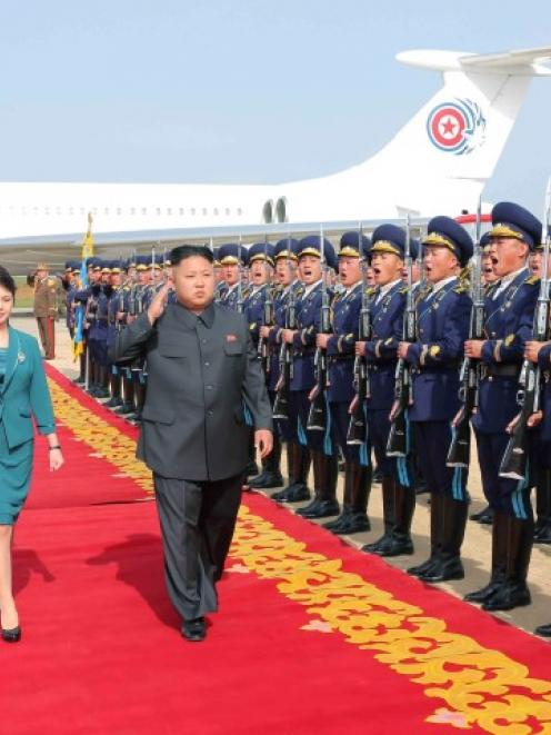 North Korean leader Kim Jong Un salutes as he and his wife Ri Sol Ju walk past a guard of honour...