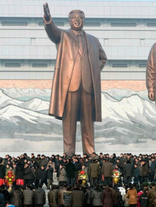 North Koreans gather in front of bronze statues of North Korea's founder Kim Il Sung (L) and late...