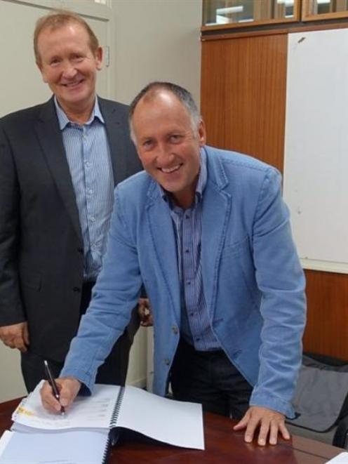 North Otago Irrigation Company chairman Leigh Hamilton (front) signs the $48 million major...