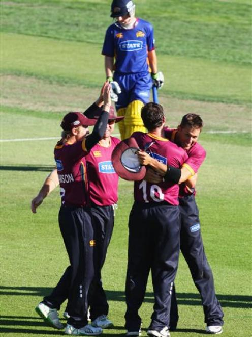 Northern Districts players celebrate winning the one-day final while a dejected Otago...