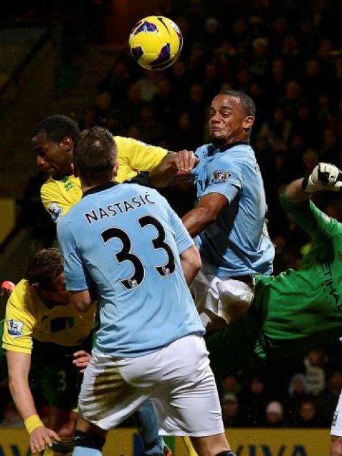 Norwich City players force a save by Manchester City's goalkeeper Joe Hart (3rd R) during their...
