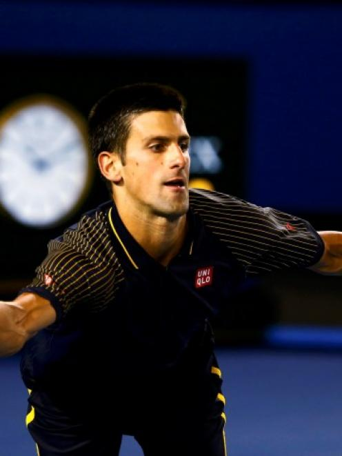 Novak Djokovic of Serbia hits a return to Ryan Harrison of the US during their men's singles...