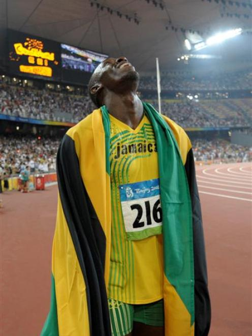 Nugget-fan Usain Bolt celebrates winning the gold and setting a new world record in the men's...