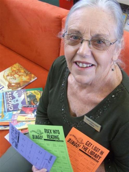 Oamaru Public Library youth librarian Alison Sofield holds book bingo cards for the competition...