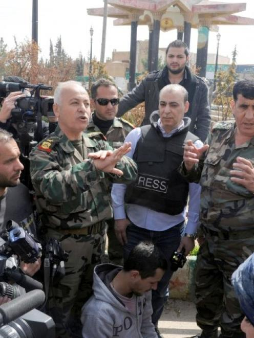 Officers loyal to Syria's President Bashar al-Assad talk to the media at Yabroud town.  REUTERS/SANA