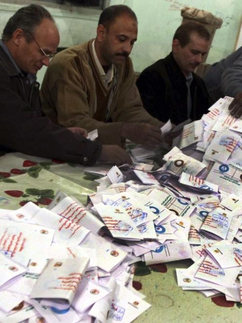Officials count ballots after polls closed in Bani Sweif, about 115km south of Cairo. Photo by...