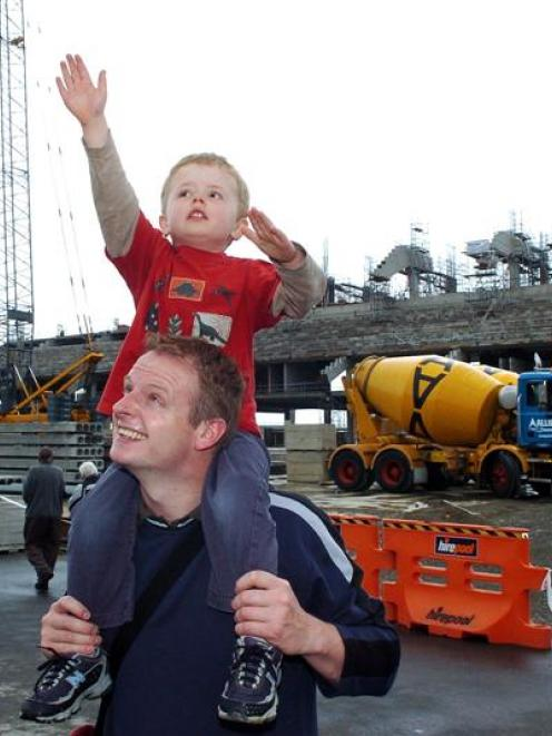 Oliver Hobbs (3), with father Tom, stretches towards one of the cranes on site at Forsyth Barr...