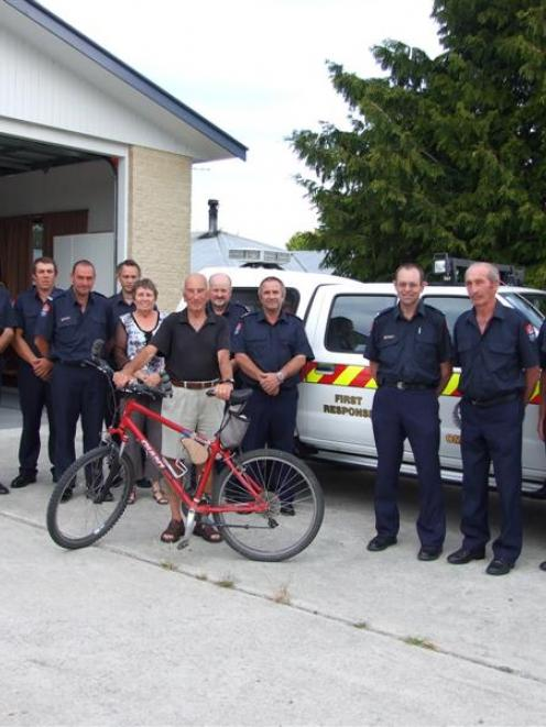 Omakau cyclist Iain Hickey (centre, holding bike) donated $700 to the Omakau Fire Brigade for the...