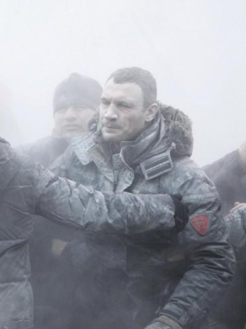 Opposition leader Vitaly Klitschko (C) reacts after he was sprayed with a powder fire...