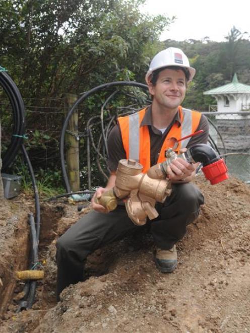 Opus engineering geologist Shane Greene holds a backflow preventer valve at Ross Creek reservoir,...