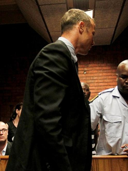 Oscar Pistorius (C) is escorted by police during a court appearance in Pretoria on Friday....