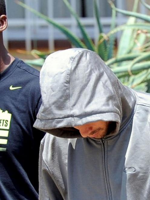 Oscar Pistorius (R) is escorted by police after an incident in which his girlfriend, model Reeva...