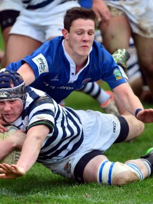 Otago Boys' High School flanker Riley McDowall scores a try despite the attentions of Southland...
