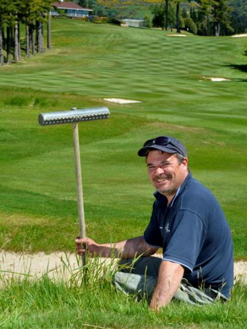 Otago Golf Club golf course manager Craig Parata takes a break from smoothing the sand in a...