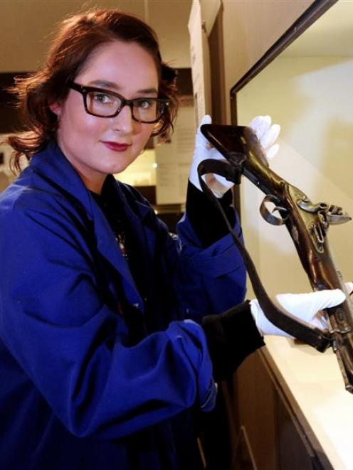 Otago Museum collection officer Jamie Metzger holds a 19th century blunderbuss, being prepared...