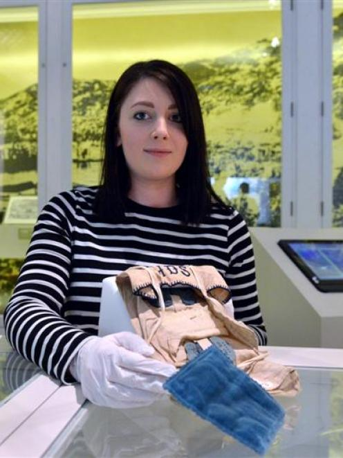Otago Museum design services officer Annah Taggart holds a sewing repair kit once used by former...