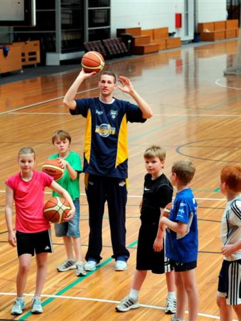 Otago Nugget Luke Aston passes on some shooting tips to members of the Diggers junior basketball...
