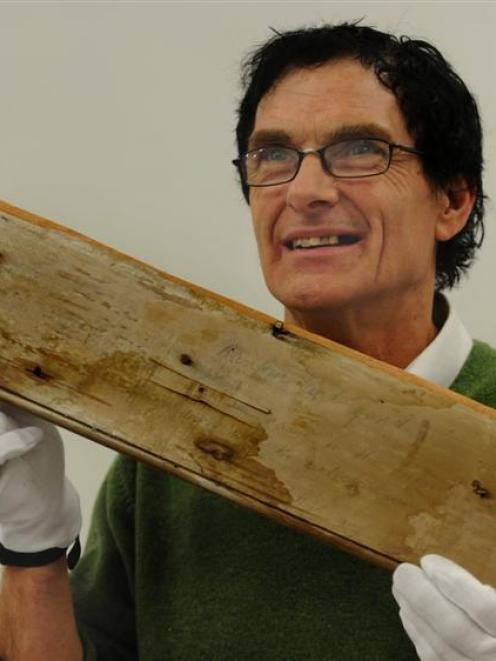 Otago Settlers Museum assistant conservator Laurence Le Ber with a  piece of graffiti from an...