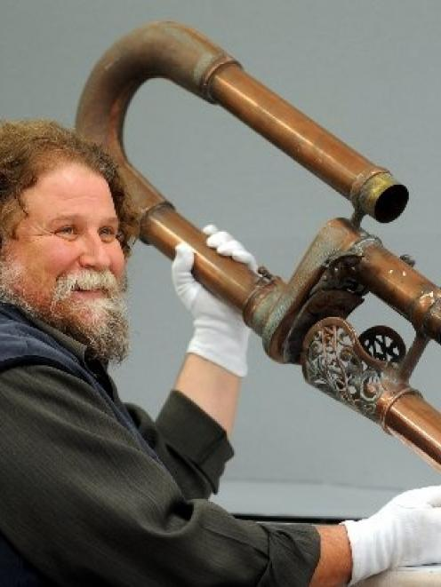 Otago Settlers Museum senior conservator Francois Leurquin holds pneumatic tubes, once part of an...