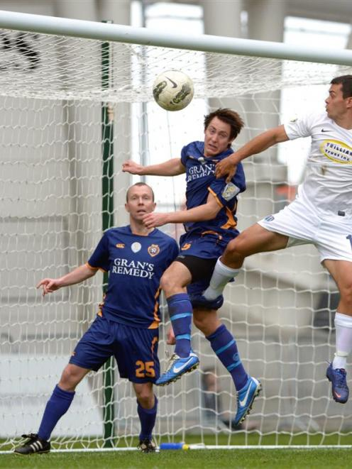 Otago United's Thomas Connor (centre) heads clear on the goal-line, watched by team-mate Craig...