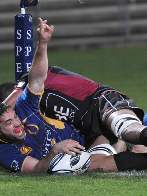 Otago winger Karne Hesketh celebrates scoring in the tackle of North Harbour lock Filo Paulo, in...