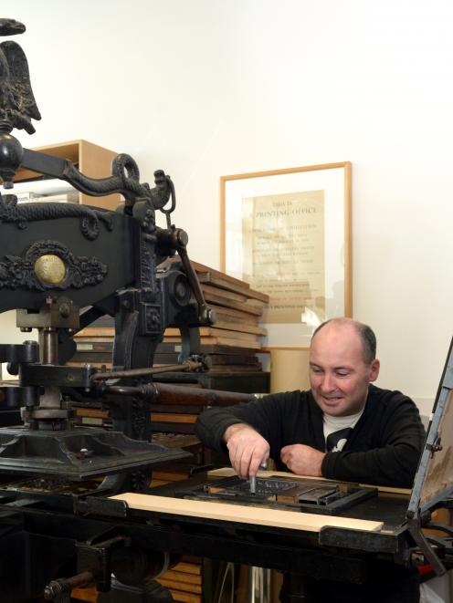 Otakou Press printer in residence Peter Vangioni works on the Columbian Eagle press in the...