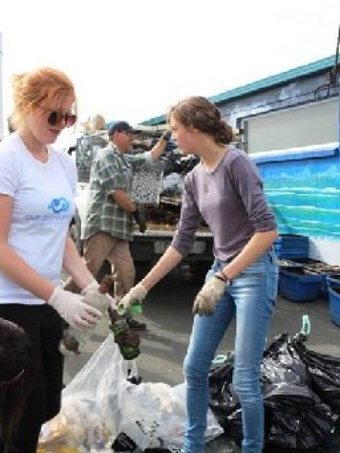 Our Seas Our Future volunteer Josie Crawshaw (centre)  and others sort rubbish collected in the...