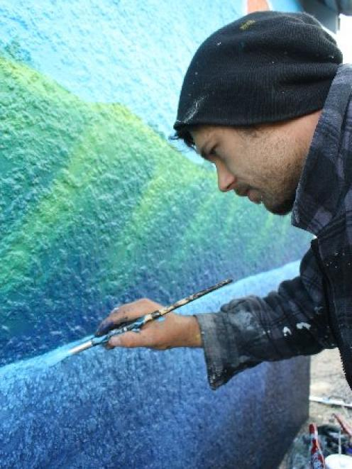 Painted tribute: Dunedin artist Daniel Mead works on his mural at the Company Bay bus shelter....