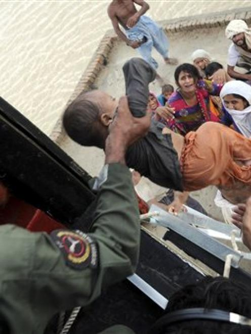 Pakistani army soldiers in a helicopter rescue families stranded by flood water in Sanawan near...