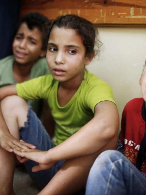 Palestinian children who fled what medics said was Israeli shelling that hit a UN-run school...