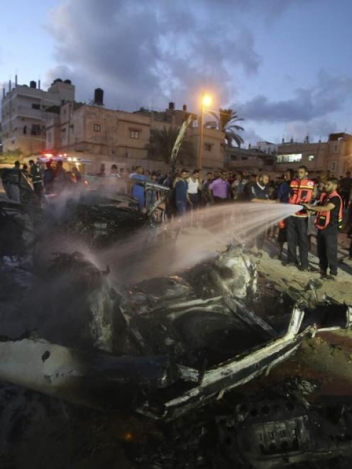 Palestinian firefighters put out a fire in a car, which witnesses said was targeted in an Israeli...
